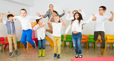 Photo pour Group of happy cheerful children with their female teacher jumping together in schoolroom - image libre de droit
