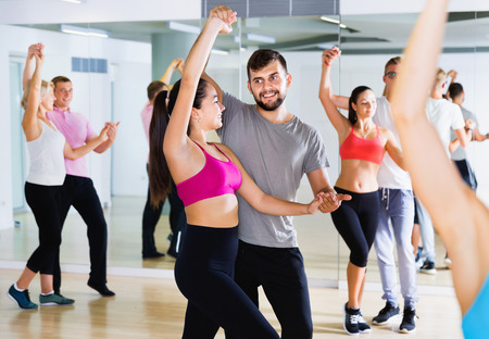 Happy cheerful positive   people  of different ages  having dancing class in classroom