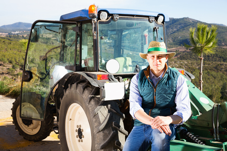 Photo pour Confident glad  positive smiling male owner of vineyard posing near tractor outdoors in sunny day - image libre de droit