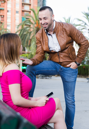 Photo pour Young male is acquaintance with girl who is sitting on bench in the park. - image libre de droit