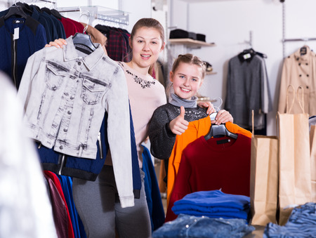 Positive woman with daughter holding many bags after shopping in clothing store