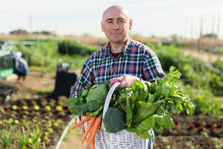 Foto für Man farmer with a basket of vegetables in the garden - Lizenzfreies Bild
