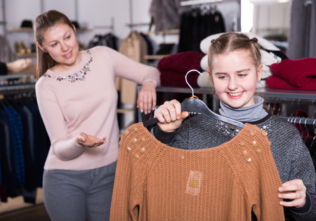 Preteen girl looking closely at new knitted sweater during shopping with her mother in clothing shop