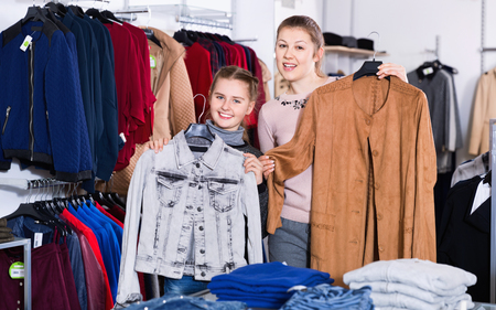 Happy cheerful positive smiling woman and her satisfied daughter enjoying shopping, holding garments bought in clothes store