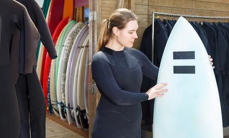 Photo pour Portrait of happy female wearing surf suit, standing with surfboard - image libre de droit