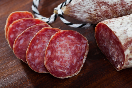 Foto de Spanish longaniza salami sausages cut in slices on a woodefn desk, close-up - Imagen libre de derechos