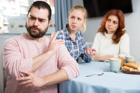 Photo pour Adult guy having argue with wife and mother-in-law - image libre de droit