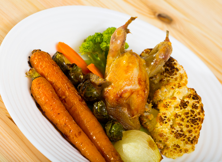 Grilled wildfowl with roasted vegetables in honey-mustard sauce served on white plate