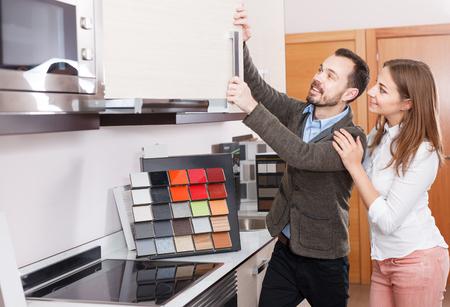 Photo pour Young couple looking material for kitchen furniture in salon - image libre de droit