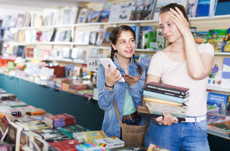 Positive schoolgirl chatting on screen tablet and shopping literature books with mother