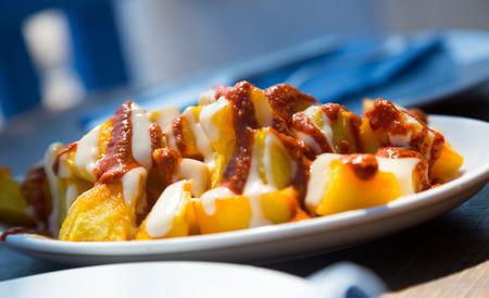 Foto de Fried pieces of potatoes in sauce original and tasty dish in Spain - Imagen libre de derechos