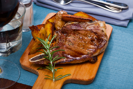 Spicy well done roasted veal entrecote with fried potato wedges and rosemary