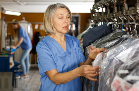 Photo pour Portrait of cheerful female laundry worker at her workplace - image libre de droit