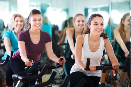 Foto für Positive happy females of different age training on a exercise bikes together - Lizenzfreies Bild