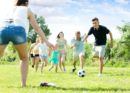 Photo pour Positive parents with four kids playing soccer together on green field on summer day - image libre de droit