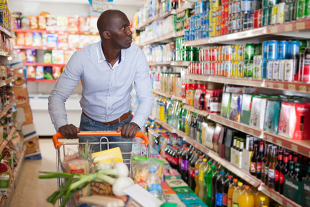 Foto für Portrait of young African male with grocery cart buying food products in supermarket - Lizenzfreies Bild