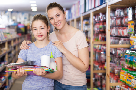 Attractive young woman with preteen girl visiting shop of stationery in search of school supplies