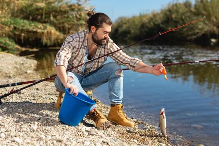 Photo pour Positive fisherman holding catch freshwater fish in hands - image libre de droit