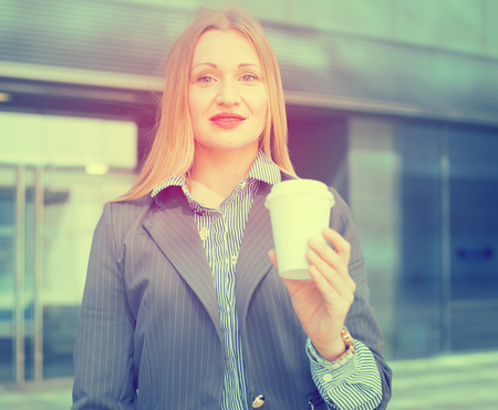 Photo pour Smiling businesswoman in suit with cup of coffee in the hand - image libre de droit
