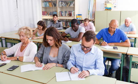 Photo pour Glad students mixed age listening task for exam in the classroom - image libre de droit