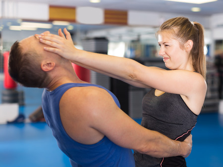Photo pour Cheerful woman is fighting with trainer on the self-defense course for woman in sport club - image libre de droit