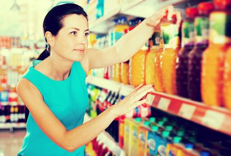 Photo pour Attractive young woman choosing fruit juice on supermarket shelf - image libre de droit