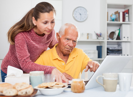 Photo pour Portrait of father and adult daughter at table using laptop together - image libre de droit