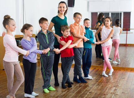 Photo pour Happy positive children dancing folk dance  in studio smiling and having fun - image libre de droit