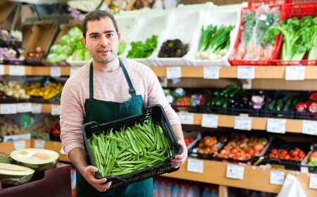 Foto für Young smiling glad friendly male seller standing with box of green beans on the supermarket - Lizenzfreies Bild