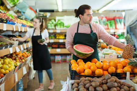 Photo pour Young salesman working with fresh fruits  in fruit store, woman on background - image libre de droit