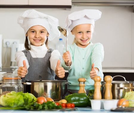 Photo for Two little american girls preparing vegetables and smiling indoors - Royalty Free Image