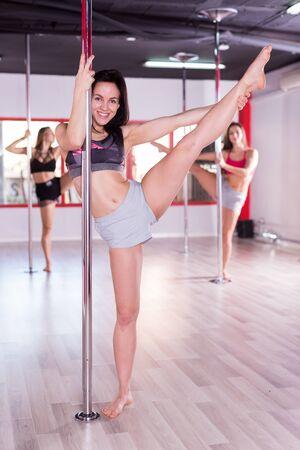 Photo pour Active females pole dancers exercising dance moves in studio - image libre de droit