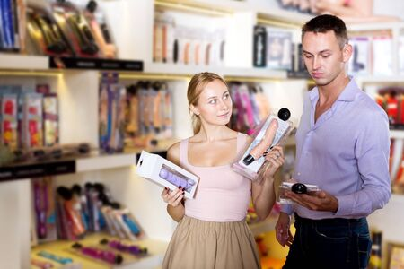 Photo for Portrait male consultant advising customer shopping sex toy in store for adults - Royalty Free Image