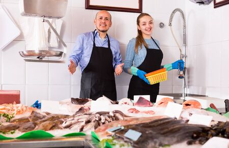 Photo pour Ordinary fish and seafood store with two friendly smiling sellers at the counter - image libre de droit
