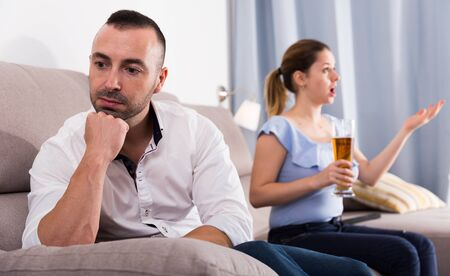 Man is sading when his wife is watching TV at home.
