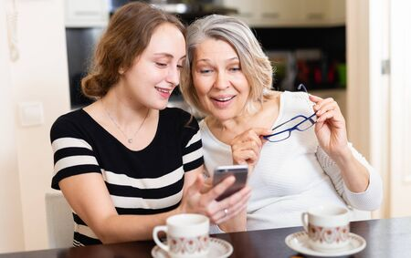 Photo for Mature mother with adult daughter sitting with smartphone in kitchen interior - Royalty Free Image