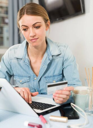 Photo pour Girl buying online with laptop and credit card at home - image libre de droit