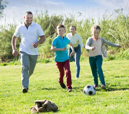 Photo for Happy parents with two kids playing soccer on the green field. Focus on man - Royalty Free Image