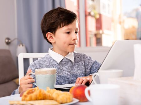 Photo pour Teenager plays on laptop in kitchen interior - image libre de droit