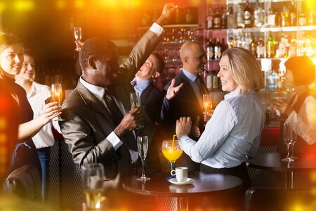 Cheerful African businessman having fun with mature female coworker during office party at nightclub