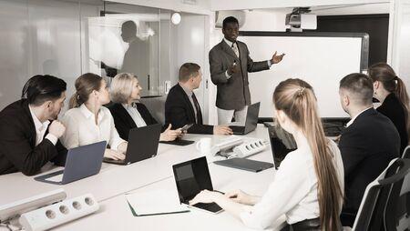 African American male speaker giving talk on corporate business meeting in meeting room