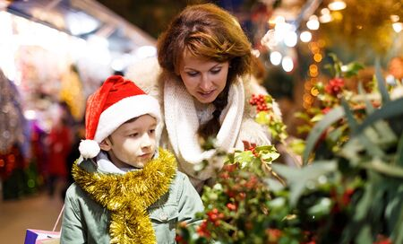 Happy school age boy with mother selecting decoration for home on Christmas market