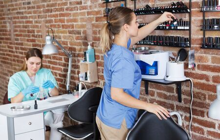 Young smiling girl manicurist standing at her workplace in modern the nail salon