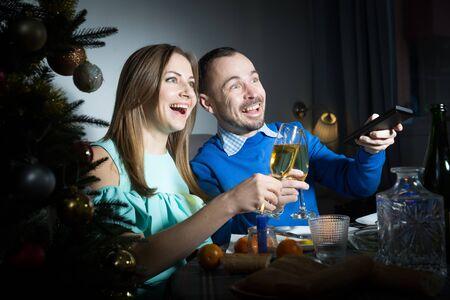 Photo pour Christmas portrait of couple celebrating holiday and watching tv - image libre de droit