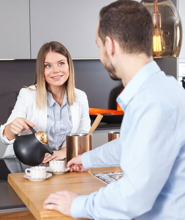 Happy young woman pouring coffee to her male guest in modern kitchen interior