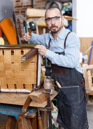 Professional male carpenter upholstering vintage armchair in repair shop