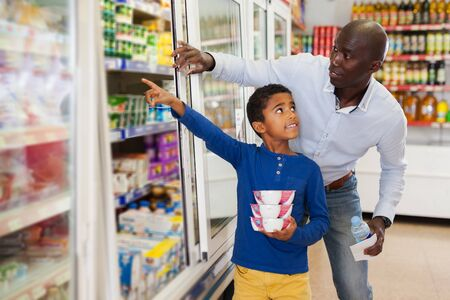 Photo pour cheerful adult African American man with his little son making purchases together in grocery - image libre de droit
