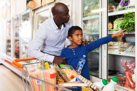 Photo pour Focused African tween boy helping his father choose fresh vegetables in grocery store. Focus on man - image libre de droit