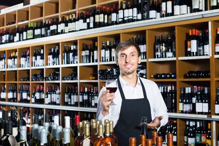 portrait of friendly smiling male seller in uniform promoting to taste wine before purchasing it in wine store