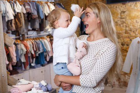 Young mother holding little daughter in her arms in baby clothing store